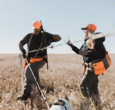 Two bird hunters work to safely cross a barbed wire fence