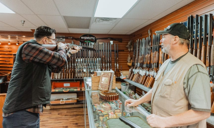 A bird hunter shoulders a used shotgun to see how it fits.