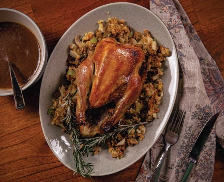 A roasted pheasant with cornbread stuffing and gravy ready to serve for dinner.
