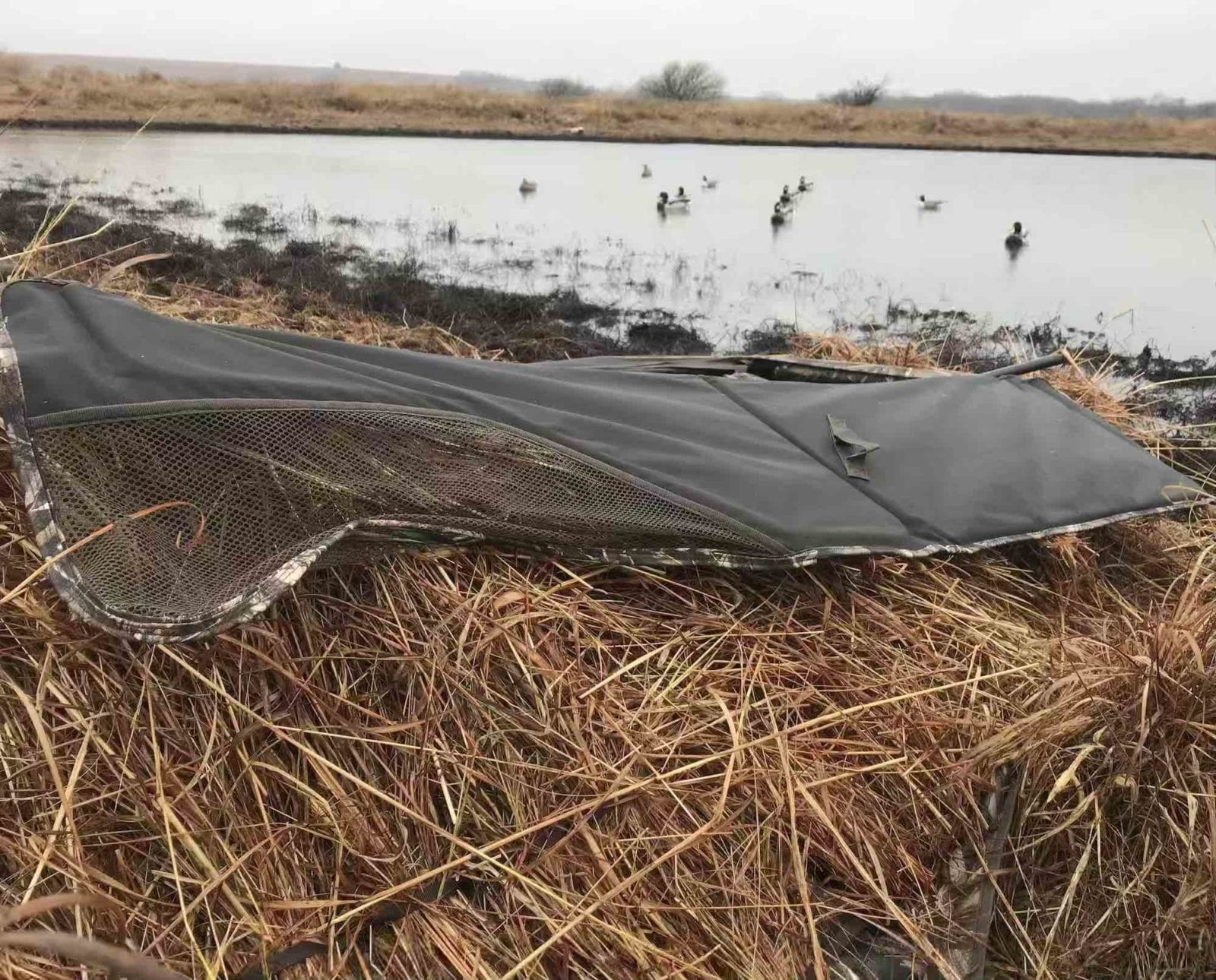 A layout blind for duck hunting next to decoys on a pond