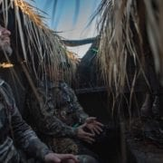 Duck hunters wait in a hunting blind with a black Labrador retriever