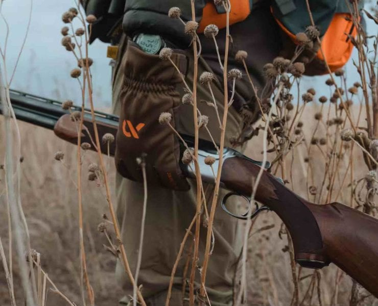 A bird hunter carries a Ruger Red Label shotgun in the field