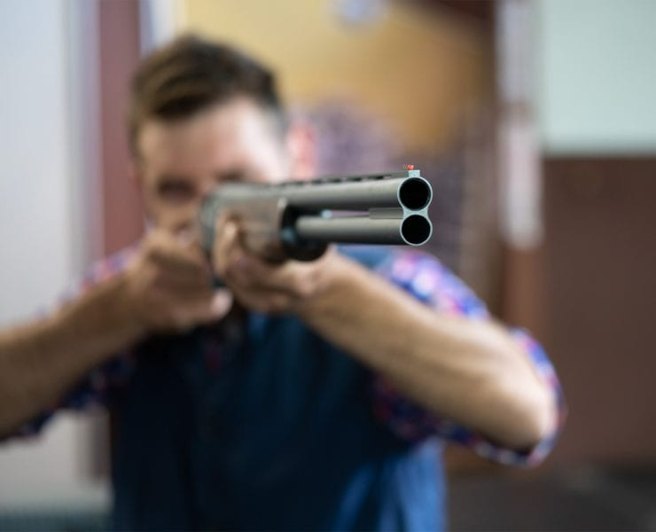 A man shoulders and over-under shotgun at the RFM factory.