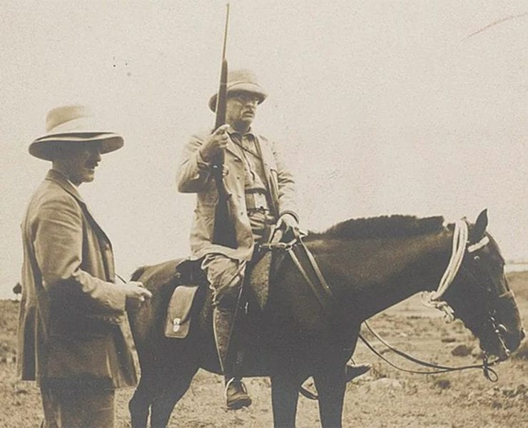 Theodore Roosevelt sits atop his horse with his custom Springfield M1903 rifle.