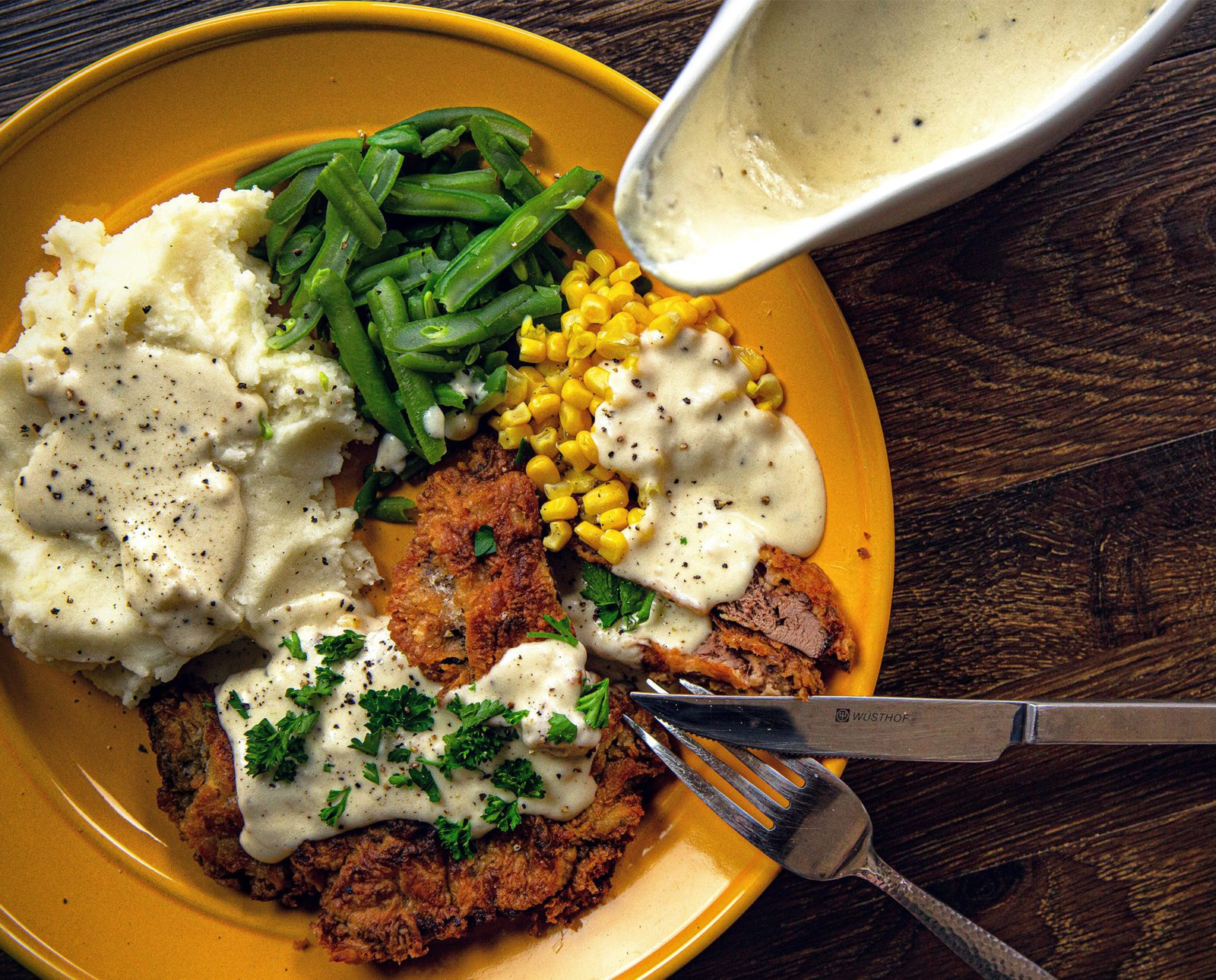 Chicken fried prairie chicken sits on a plate with sides.